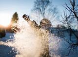 child tosses snow in winter sunlight