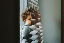 Kid Hiding Behind The Window B...