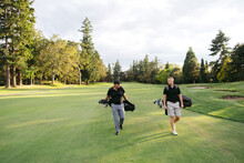 Two Men Walking On Golf Course.