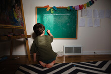 Child Writes Letters On Chalkboard