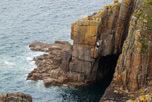 At The Rocky Atlantic Coast Of Cornwall, There Are Numerous Promontories With Scenic Rock Formations. Cracked Mossy Rocks Seem As If They Are Staggered Blocks. Also There Is A Sea Cave Underneath.
