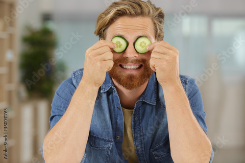 Fototapeta funny man playing with cucumber on eyes obraz