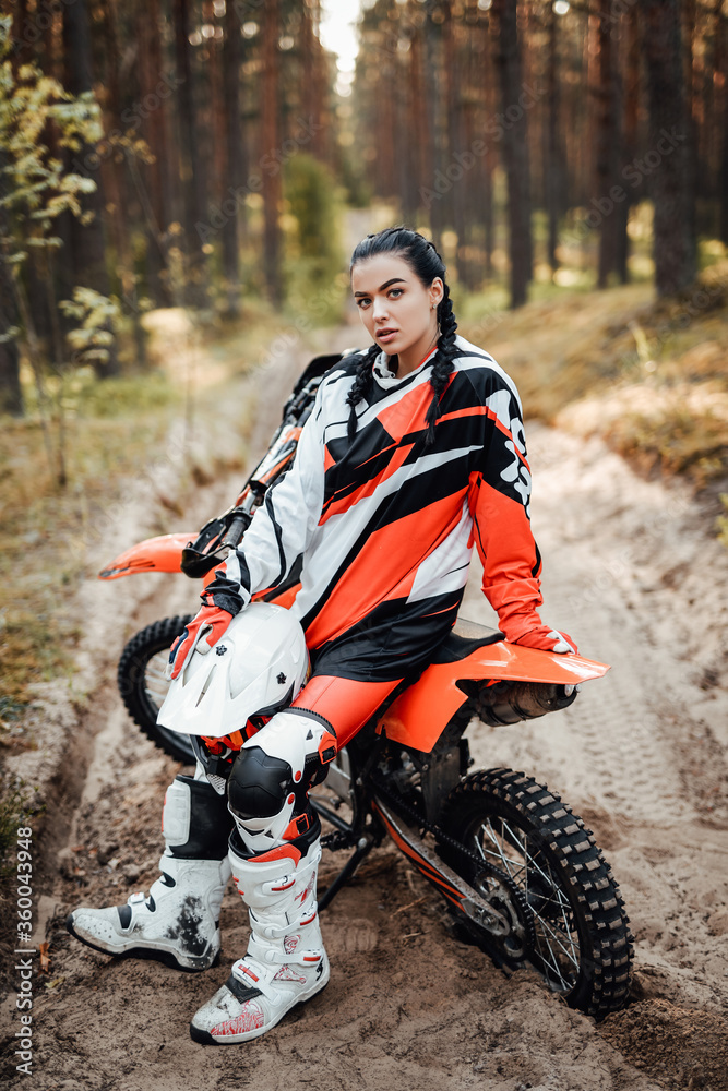 Fototapeta Beautiful young female racer sitting on her motocross bike on a trail of sand in the woods