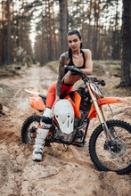Tattooed Female Racer Wearing Motocross Outfit With Semi Naked Torso Sitting On Her Bike In The Forest