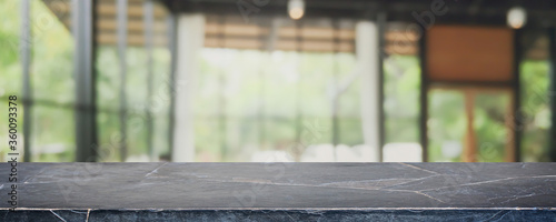 Fototapeta Empty black marble stone table top and blurred coffee shop, cafe and restaurant interior background - can used for display or montage your products. obraz