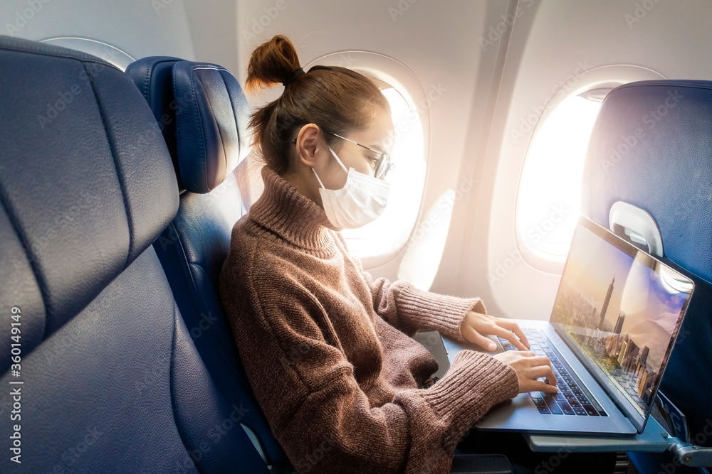 Fototapeta A young woman wearing face mask is traveling on airplane , New normal travel after covid-19 pandemic concept