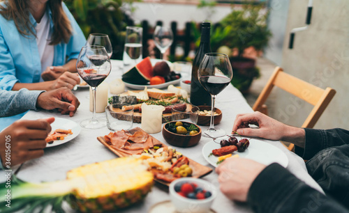 Obraz Group of young people dressed in casual clothes dining together drinking red wine and eating snacks, fruits, Friends celebrating birthday sitting in restaurant with small garden enjoying atmosphere - fototapety do salonu