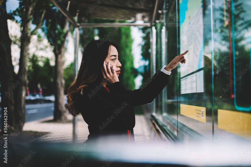 Fototapeta Pensive female tourist using mobile connection in roaming calling to friend while searching route of public transport on maps on bus stop, concentrated woman waiting for bus checking schedule