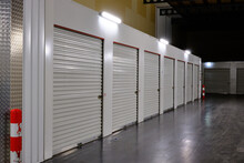 Row Of White Doors Indoor Storage Units In A Self Storage Facility. Rental Storage Units With Red White Safety Pole. Netherlands