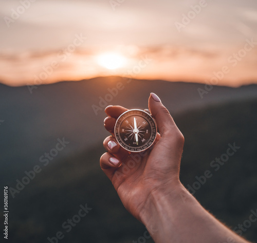 Tablou Canvas Woman hand with magnetic compass in summer mountains at sunrise, pov