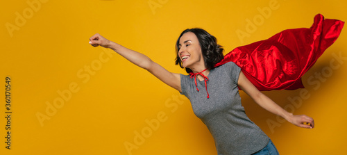 To new adventures! A young, beautiful girl, pretending she is a superwoman, and flying in a classic superman pose, but with superman red cloak, that is flattering on the wind Wallpaper Mural