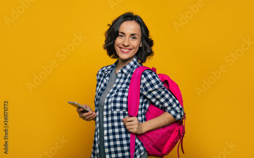 Tablou Canvas Student's life! A half-length photo of a young beautiful student, dressed casually, with her cute, pink backpack on her one shoulder, looking with a wide smile, holding her smartphone in her hand