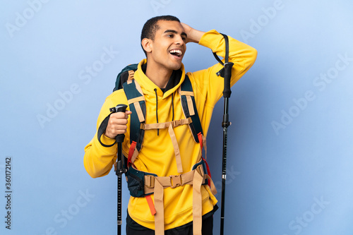 Fototapeta African American man with backpack and trekking poles over isolated background smiling a lot obraz