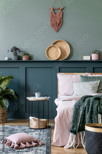 Stylish composition of bedroom interior with wooden bed, design furnitures, shelf, plants, decor and elegant personal accessories. Beautiful bed sheets, blanket and pillow. Template. Home staging.