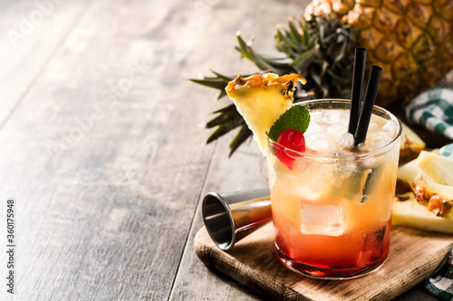 Cold mai tai cocktail with pineapple and cherry on wooden table. Copy space