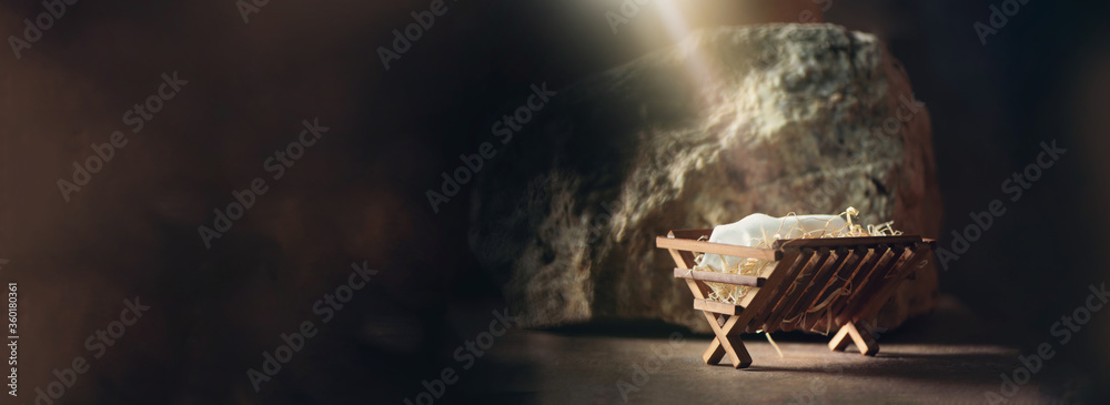 Fototapeta Christian Christmas concept. Birth of Jesus Christ. Wooden manger in cave background. Banner, copy space. Nativity scene symbol. Jesus is reason for season. Salvation, Messiah, Emmanuel, God with us