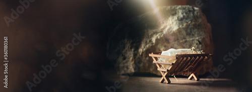 Fototapeta Christian Christmas concept. Birth of Jesus Christ. Wooden manger in cave background. Banner, copy space. Nativity scene symbol. Jesus is reason for season. Salvation, Messiah, Emmanuel, God with us obraz