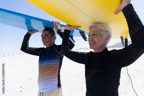 Senior Caucasian couple holding surfboards at the beach.