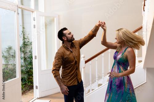 Slika na platnu Caucasian couple having fun dancing and smiling in the hallway