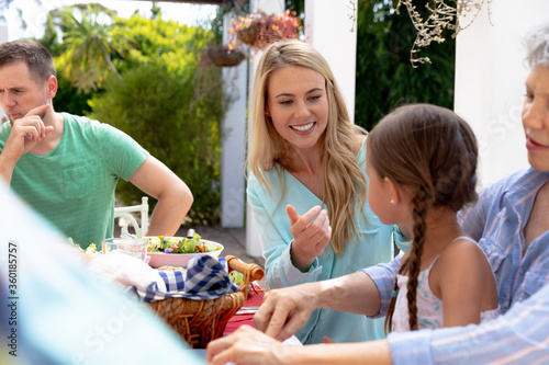 Caucasian family sitting at table during a family lunch in the garden Fototapete