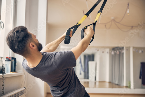 Fototapeta Sportsman working out using a suspension trainer