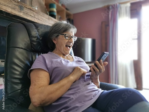 Senior woman, 82-year-old grandmother with glasses happy, handling a mobile device for entertainment and communication with children and grandchildren
