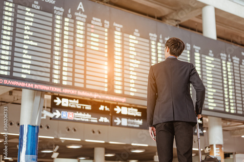 Cuadros en Lienzo Businessman standing at time flight schedule billboard hold the smartphone at airport terminal gate