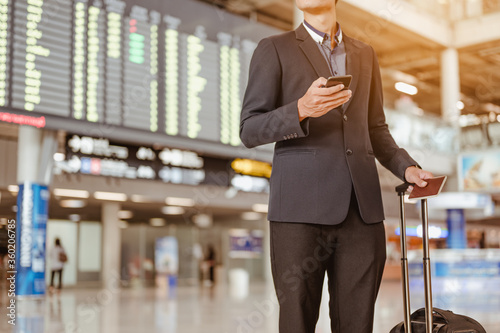Fotografía Businessman standing at time flight schedule billboard hold the smartphone at airport terminal gate