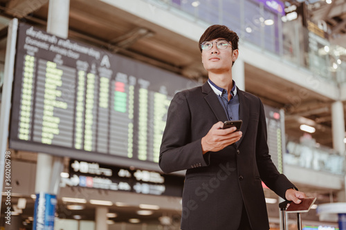 Fotomural Businessman standing at time flight schedule billboard hold the smartphone at airport terminal gate