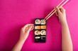 Female hand holding chopsticks and mobile phone with tasty sushi roll on screen against color background. Online food delivery concept. Copy space
