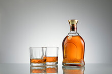 Close Up View Of Bottle Of Whiskey And A Glasses Aside On Grey Back.