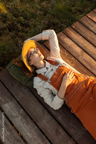 Fotografering Woman naturalist in beige hat and orange overalls resting lying on a backpack on wooden path through peat bog swamp in wildlife national park at sunset