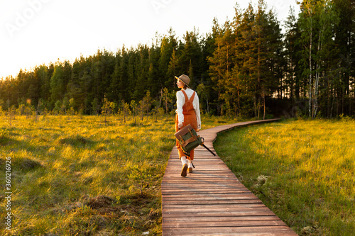 Cuadros en Lienzo Woman botanist with backpack on ecological hiking trail in summer outdoors