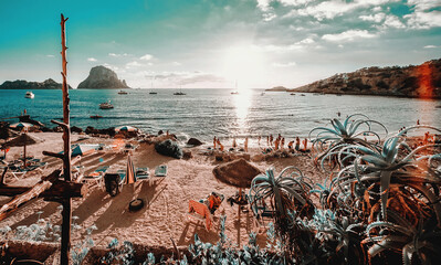 View of Cala d'Hort Beach in Ibiza. Unrecognizable tourists relaxing hanging out on the picturesque famous seaside with Es Vedra rock picturesque view during sunset. Balearic Islands. Espana, Spain