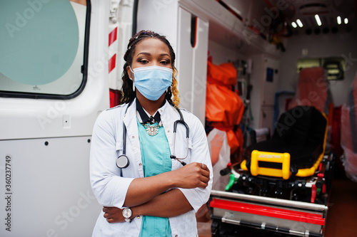 Fotografiet African american female paramedic in face protective medical mask standing in front of ambulance car