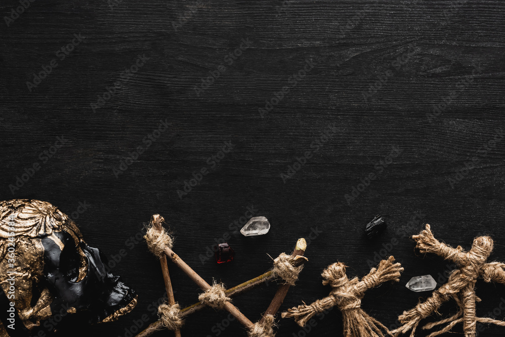 Fototapeta top view of voodoo dolls, ancient crystals, pentagram and skull on black