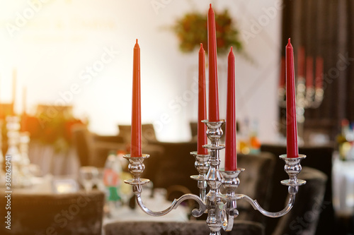 Leinwand Poster On the table is a candlestick made of metal with red candles