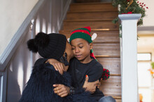 Affectionate Mother Kissing Son In Christmas Hat On Stairs