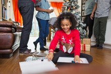 Excited Girl Opening Christmas Gift On Living Room Floor