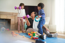 Mother And Kids Exercising In Living Room