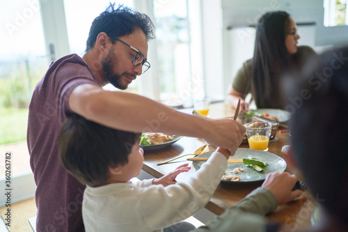 Father helping son cut food at dinner table - 360263782