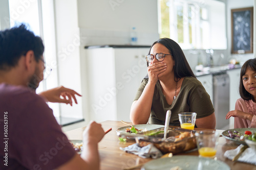 Happy family laughing at dinner table - 360263976