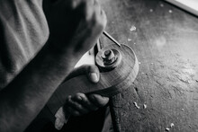 Black And White High Angle Of Faceless Craftsman Carving Swirl Of Violin Head While Working With Wooden Detail Using Bit At Table In Workshop