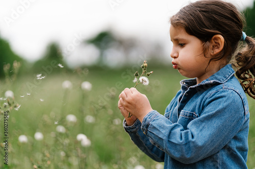 Side view of child in denim jacket blowing flower seeds while standing on meadow in summer - 360275585