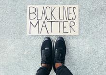 Feet Detail Besides A Black Lives Matter Sign On Floor. A A Gesture Against Racism