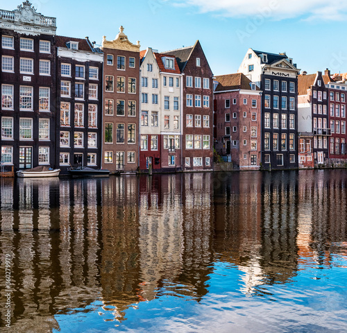 Traditional buildings along the Damrak reflected in the canal, Amsterdam, the Netherlands - 360279979