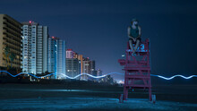 Man Sitting On Lifeguard Chair Against Sky At Night, Daytona, Florida, USA