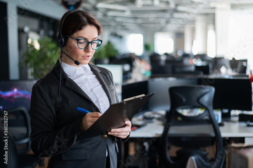 Vászonkép Serious business woman in a suit answers the customer's call on the headset