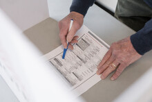 High Angle View Of Senior Man Filling Out Ballot In Voting Booth