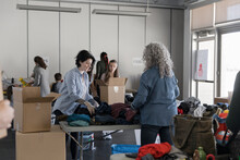Volunteers Sorting Donations For Clothes Drive In Community Center